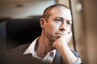 Thoughtful mature businessman sitting in train - MASF05367