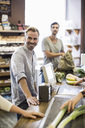 Smiling man standing at supermarket checkout counter with friend in background - MASF05379