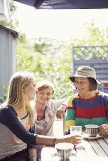 Three generation females having coffee in yard - MASF05388