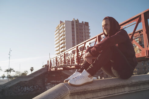 Man with hoodie sweater sitting on wall - SKCF00432