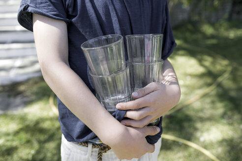 Boy standing in garden holding empty glasses, partial view - KMKF00191