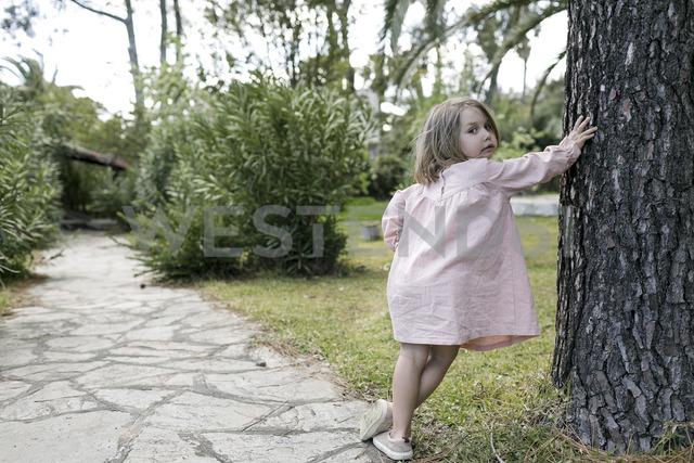 Portrait of little girl leaning against tree trunk in garden - KMKF00194