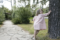 Portrait of little girl leaning against tree trunk in garden - KMKF00194