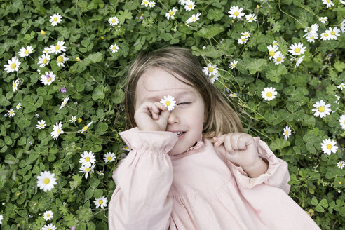 Portrait of little girl lying on flower meadow - KMKF00197