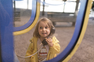 Portrait of little girl using telephone booth - KMKF00203