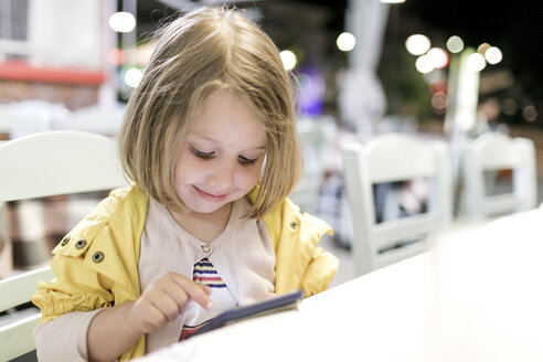 Portrait of smiling little girl sitting in a restaurant playing with smartphone - KMKF00206