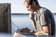 Profile shot of mature man using laptop on pier - MASF05435
