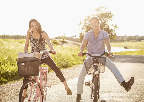 Portrait of happy young couple with legs apart cycling on country road - MASF05438