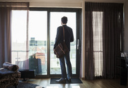 Rear view of businessman looking through window in hotel room - MASF05459