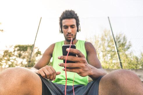 Basketball player listening music, smartphone and headphones - FMOF00335