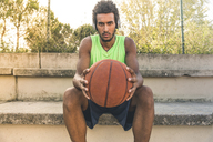 Young basketball player holding ball and listening music - FMOF00338