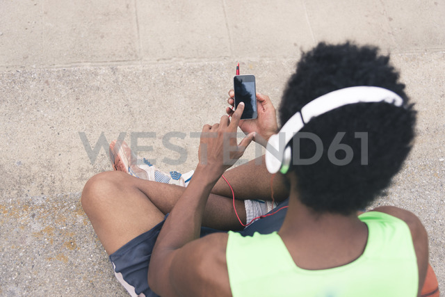 Basketball player listening music, smartphone and headphones - FMOF00356