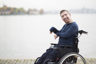 Portrait of happy man with cerebral palsy sitting on wheelchair by lake - MASF05498