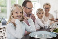 Portrait of happy girl sitting with family at dining table - MASF05501