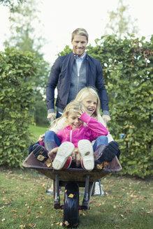 Playful father pushing daughters on wheelbarrow at yard - MASF05504