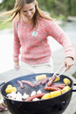Mid adult woman barbecuing outdoors - MASF05528