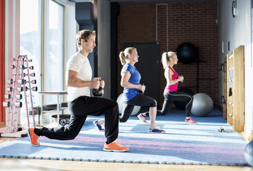 People exercising with kettlebells at gym - MASF05537