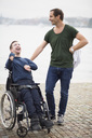 Male caretaker standing with happy disabled man on wheelchair by lake - MASF05558