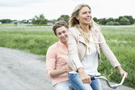 Happy young couple enjoying bicycle ride at countryside - MASF05591