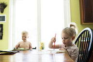 Siblings painting by table at home - CAVF43042