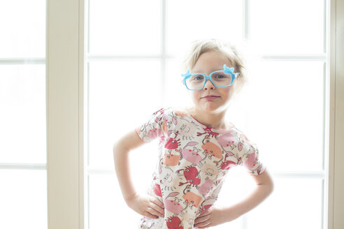 Portrait of girl wearing eyeglasses standing by window at home - CAVF43045
