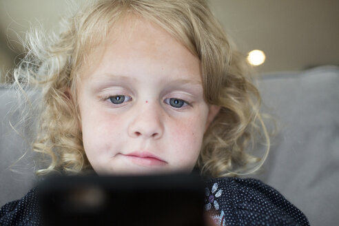 Low angle view of girl using tablet computer on bed at home - CAVF43057