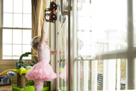 Girl playing with toy car on window at home - CAVF43120