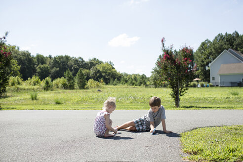 Siblings writing with chalk on road against sky during sunny day - CAVF43132