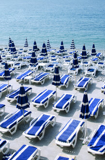 High angle view of deck chairs with parasols arranged at beach during sunny day - CAVF43168