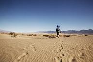 Rear view of boy walking at desert against clear blue sky - CAVF43210
