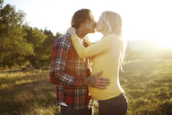 Romantic couple kissing while standing on grassy field during sunny day - CAVF43315