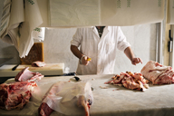 Midsection of butcher chopping meat at counter in shop - CAVF43396