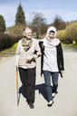 Full length of senior woman with female home caregiver walking arm in arm on street - MASF05605