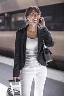 Happy businesswoman using mobile phone on railroad station platform - MASF05611