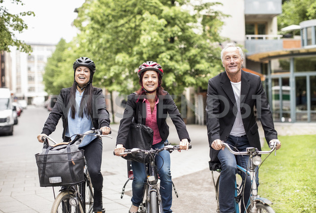 Happy business people riding bicycles on street - MASF05623