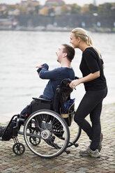 Happy disabled man with caretaker enjoying view by lake - MASF05635