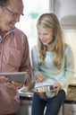 Grandfather and granddaughter using digital tablet while cooking in kitchen - MASF05638