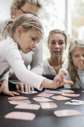 Girl playing card puzzle game with family at home - MASF05641