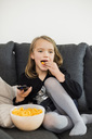 Girl eating snacks while watching TV on sofa at home - MASF05656