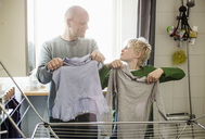 Father and son drying laundry on rack while looking at each other - MASF05662