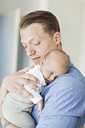 Father carrying baby girl at home - MASF05668