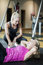 Female instructor assisting senior woman in doing sit-ups at gym - MASF05683