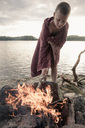 Boy wrapped in towel standing by bonfire at lake - MASF05698
