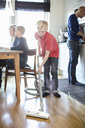 Boy vacuuming hardwood floor with family in background - MASF05704