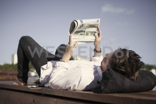 Businessman reading newspaper while lying on boardwalk - MASF05716 - Maskot ./Westend61