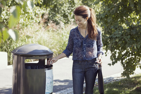 Businesswoman throwing garbage in bin at park - MASF05719
