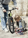 Boy filling bicycle tire with foot pump while father standing on road - MASF05725