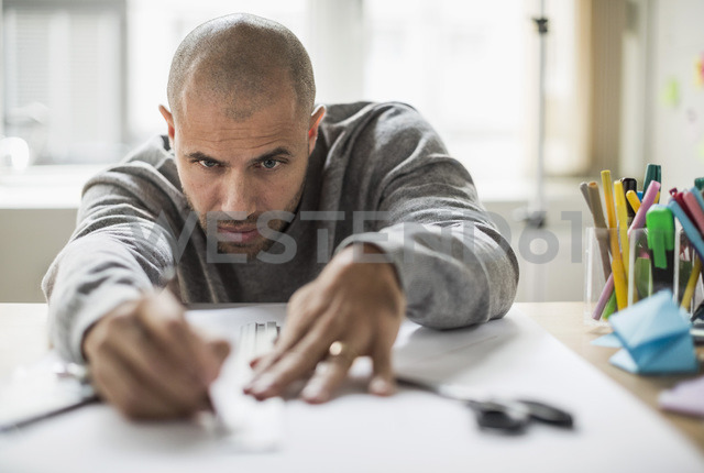 Businessman drawing line on paper at desk in creative office - MASF05779
