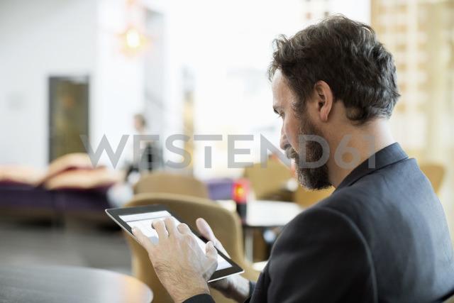 Businessman using digital tablet in hotel restaurant - MASF05821