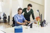 Businessmen using laptop in office - MASF05833